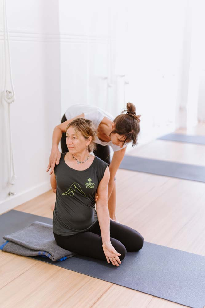 teacher demonstrating yoga pose to students